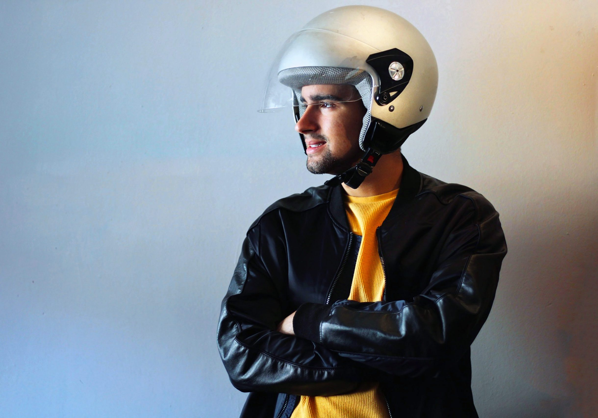 Young biker with a gray motorcycle helmet on. Road safety campaign. Copy Space.